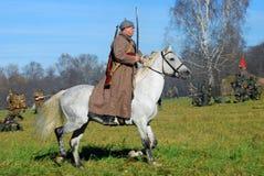 El soldado-reenactor ruso monta un caballo blanco Fotos de archivo