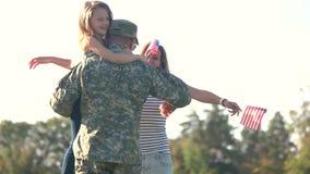 El soldado se juntó con su familia en un día soleado en el parque almacen de video