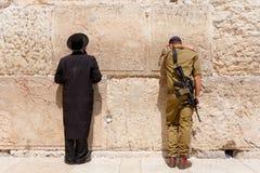 El soldado y el hombre judío ortodoxo ruegan en la pared occidental, Jerusalén