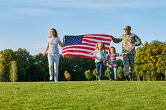 El soldado y su familia son banderas americanas que caminan que caminan Imagen de archivo libre de regalías