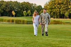 El soldado y su novia están caminando en la hierba Fotografía de archivo libre de regalías