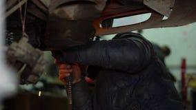 El soldador del hombre repara a la carrocería puesta de la máscara para ver el resultado sin las chispas del metal heated almacen de video