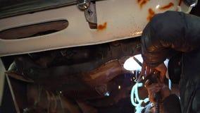 El soldador del hombre repara las chispas de las reparaciones de la carrocería del metal heated almacen de metraje de vídeo