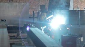 El soldador en la fábrica elabora cerveza las estructuras del metal almacen de video