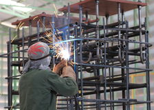 El soldador está soldando con autógena el marco de acero en fábrica Fotos de archivo