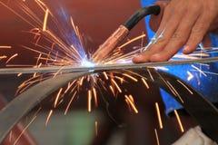El soldador está soldando con autógena la barra plana de acero sin el guante de la seguridad Foto de archivo libre de regalías
