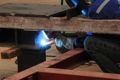 El soldador está soldando con autógena la estructura de acero con todo el equipo de seguridad Foto de archivo