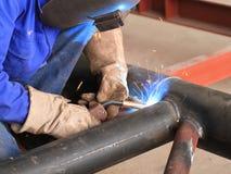 El soldador está soldando con autógena la estructura del tubo con toda la seguridad Imagen de archivo libre de regalías