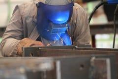 El soldador está soldando con autógena la placa de acero en fábrica Foto de archivo libre de regalías