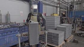 El soldador funciona en una empresa industrial La cámara vuela alrededor de él Las chispas vuelan en todas las direcciones almacen de video