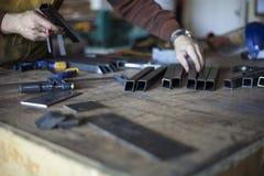 El soldador selecciona las herramientas y las piezas de acero precortadas Foto de archivo libre de regalías