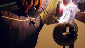 El soldador suelda con autógena dos pedazos de tubería de acero almacen de metraje de vídeo
