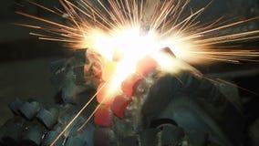 El soldador suelda con autógena las partes de la estructura del metal almacen de video