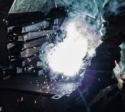 El soldador suelda con autógena las piezas de metal, muchas chispas y los humos, soldadura, arco de soldadura, flash brillante, p fotos de archivo libres de regalías