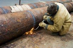 El soldador suelda con autógena segmentos del tubo Reparación y reemplazo de p anticuado foto de archivo
