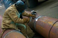 El soldador suelda con autógena segmentos del tubo Reparación y reemplazo de p anticuado imagenes de archivo
