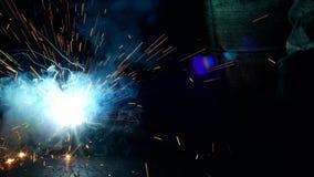 El soldador suelda con autógena una pieza de metal, muchas chispas y el humo, primer, soldadura, primer, construcción almacen de metraje de vídeo