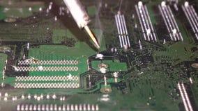 El soldar a una placa de circuito de un cierre del ordenador para arriba metrajes