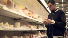 El solo hombre está tomando los paquetes con queso y carne en un supermercado y poner almacen de metraje de vídeo