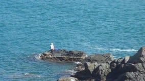 El solo hombre pesca en el mar abierto con una piedra enorme el mar es limpio y azul almacen de video