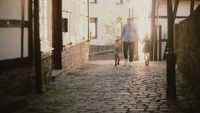 El solo padre camina con dos niños que llevan a cabo las manos Papá, muchacho y muchacha europeos junto Relaciones de familia vin almacen de video