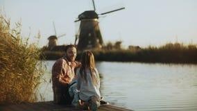 El solo papá con dos niños se sienta en un embarcadero soleado del lago Molinoes de viento holandeses tradicionales en Países Baj metrajes