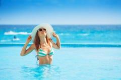 El sombrero blanco que lleva de la mujer feliz se coloca en agua de mar Foto de archivo libre de regalías