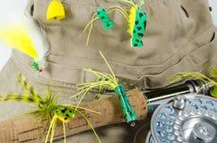 El sombrero de la pesca con la mosca Rod y el carrete con bajo vuela Imágenes de archivo libres de regalías