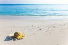 El sombrero de paja pone en la arena en el borde del mar fotos de archivo