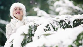 El sombrero de piel vistió mirada femenina atractiva sonriente hacia fuera y ocultando detrás de la rama spruce en el bosque almacen de video