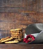 El sombrero de vago australiano del ejército y las galletas tradicionales de Anzac en oscuridad reciclaron la madera Imágenes de archivo libres de regalías