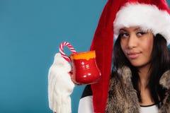 El sombrero del ayudante de santa de la muchacha del invierno sostiene la taza roja Foto de archivo