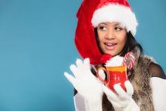 El sombrero del ayudante de santa de la muchacha del invierno sostiene la taza roja Fotos de archivo libres de regalías