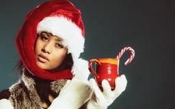 El sombrero del ayudante de santa de la muchacha del invierno sostiene la taza roja Imágenes de archivo libres de regalías