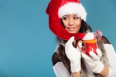 El sombrero del ayudante de santa de la muchacha del invierno sostiene la taza roja Foto de archivo libre de regalías