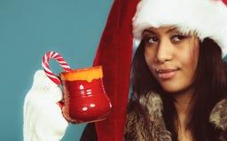 El sombrero del ayudante de santa de la muchacha del invierno sostiene la taza roja Imagen de archivo