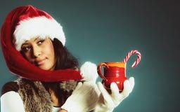 El sombrero del ayudante de santa de la muchacha del invierno sostiene la taza roja Fotografía de archivo