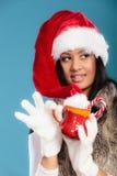 El sombrero del ayudante de santa de la muchacha del invierno sostiene la taza roja Imagenes de archivo