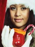 El sombrero del ayudante de santa de la muchacha del invierno sostiene la taza roja Fotografía de archivo libre de regalías