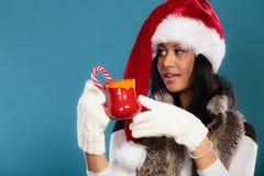 El sombrero del ayudante de santa de la muchacha del invierno sostiene la taza roja Imagen de archivo libre de regalías