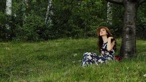 El sombrero del verano de la muchacha que lleva bonita y el vestido largo oscuro se está sentando debajo del árbol con el libro e almacen de metraje de vídeo