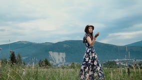 El sombrero que lleva y el vestido de la mujer bonita joven es selección las flores en fondo de las montañas almacen de metraje de vídeo