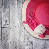 El sombrero rosado del verano con las rosas de seda florece en la textura de madera del grunge Imagen de archivo libre de regalías