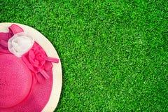 El sombrero rosado del verano con las rosas de seda florece en la textura verde de Gard Imagenes de archivo