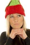 El sombrero rubio del duende de la mujer cercano mira para arriba las manos debajo de la barbilla Fotos de archivo libres de regalías