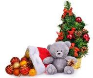 El sombrero y el árbol de navidad de Santa Claus con el oso de peluche suave de las chucherías juegan Foto de archivo libre de regalías