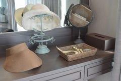 El sombrero y la joyería blancos fijaron en una tabla del aparador Fotografía de archivo