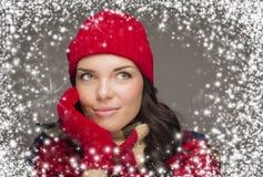 El sombrero y los guantes del invierno de la mujer de la raza mixta que llevan disfruta de las nevadas Imagen de archivo libre de regalías