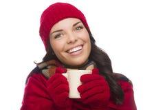 El sombrero y los guantes del invierno de la mujer de la raza mixta que llevan sostiene la taza Imagen de archivo libre de regalías