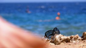 El sombrero y los vidrios en la playa de Egipto defiende en una roca el mar almacen de metraje de vídeo